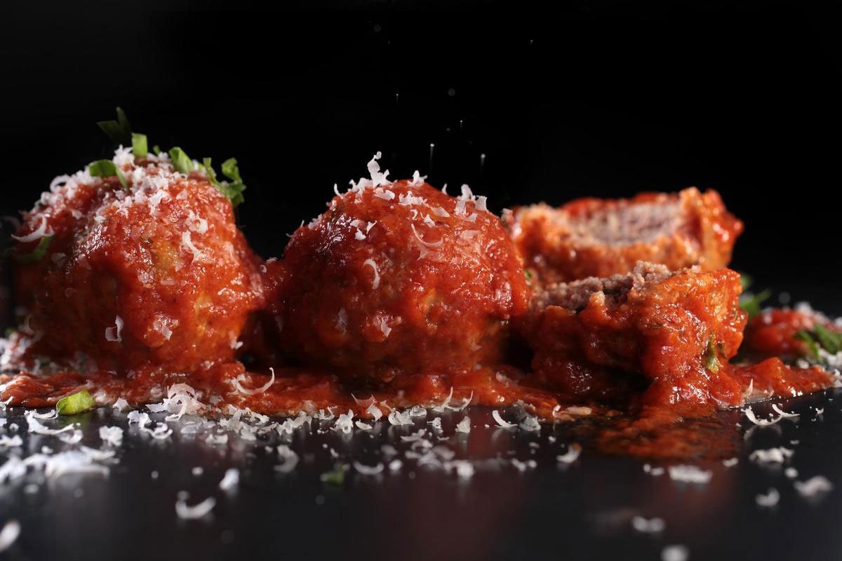 Tomato sauce and cheese over organic grass fed ground beef meatballs